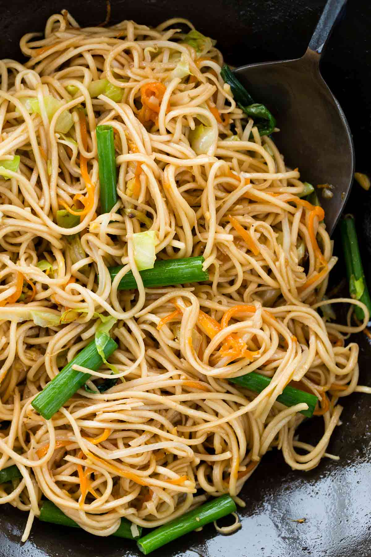 Spatula moving around chow mein noodles in a wok