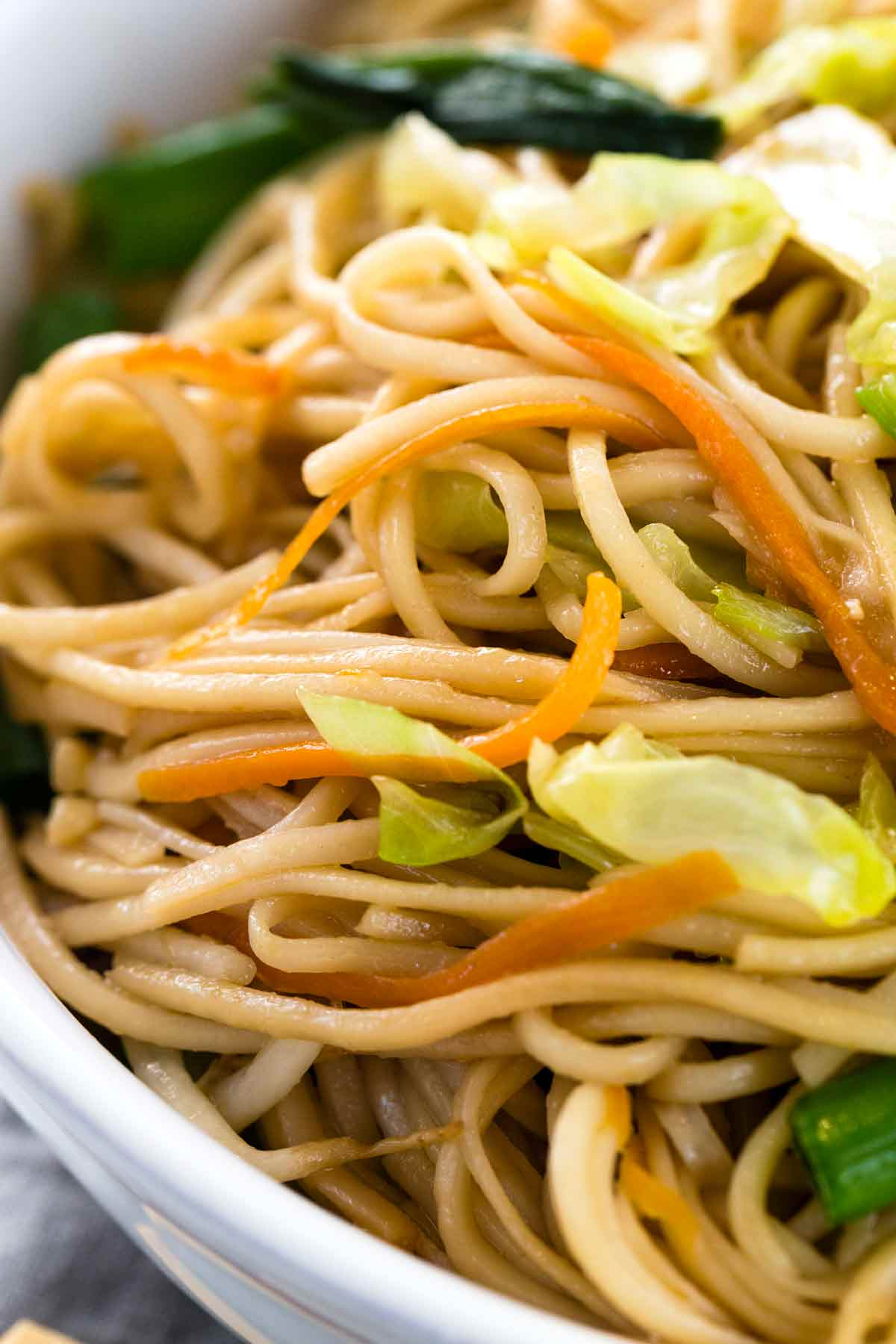 Close up photo of chow mein noodles with pieces of carrots and cabbage