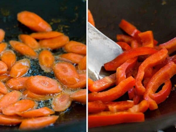 Sliced carrots and red bell peppers cooking in a wok