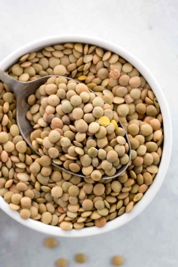 Bowl of raw brown lentils with a spoon