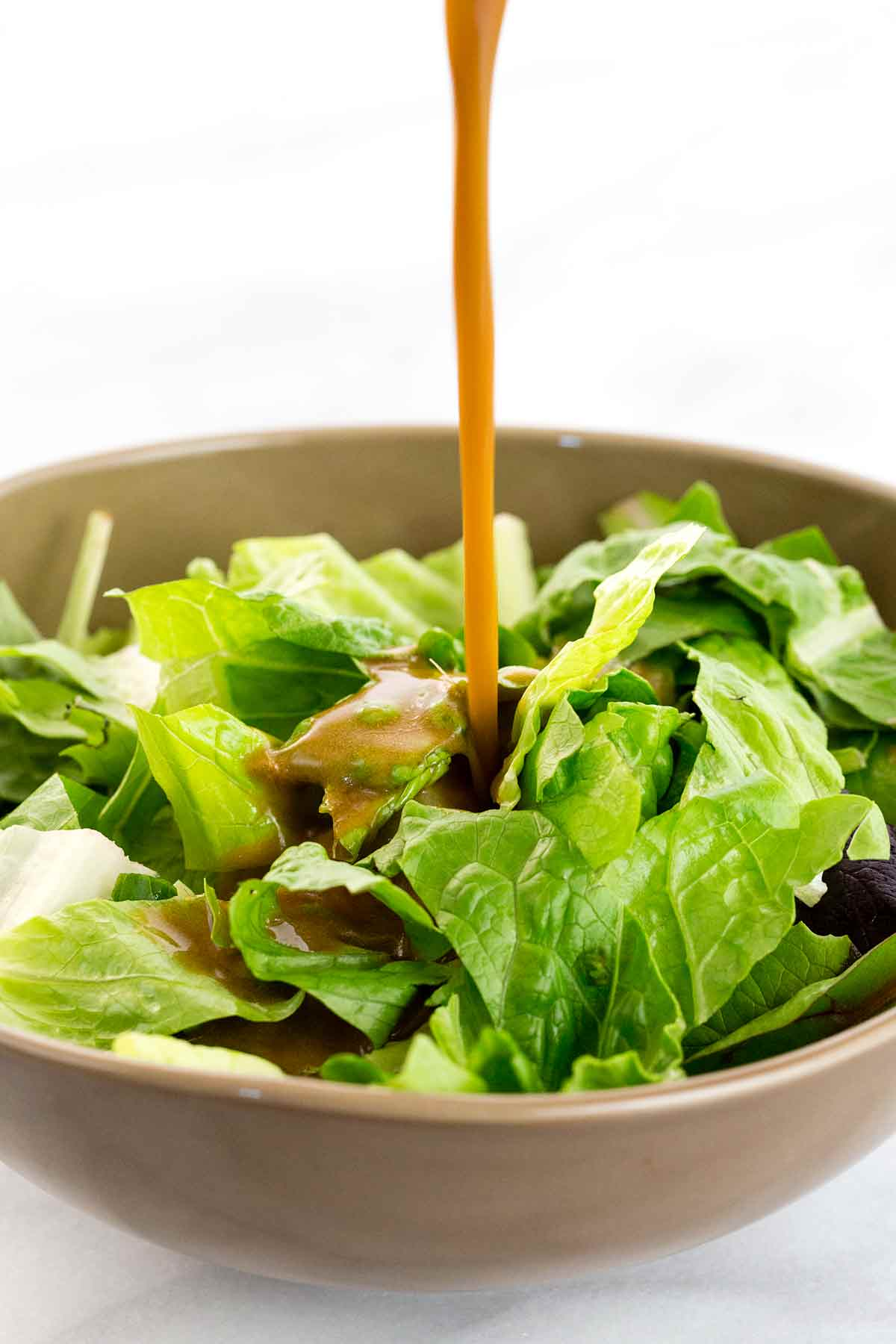 Pouring dressing onto a green salad