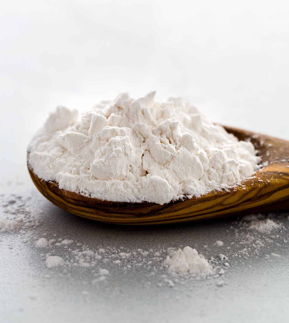 Closeup photo showing clumps of white arrowroot powder on a wooden spoon