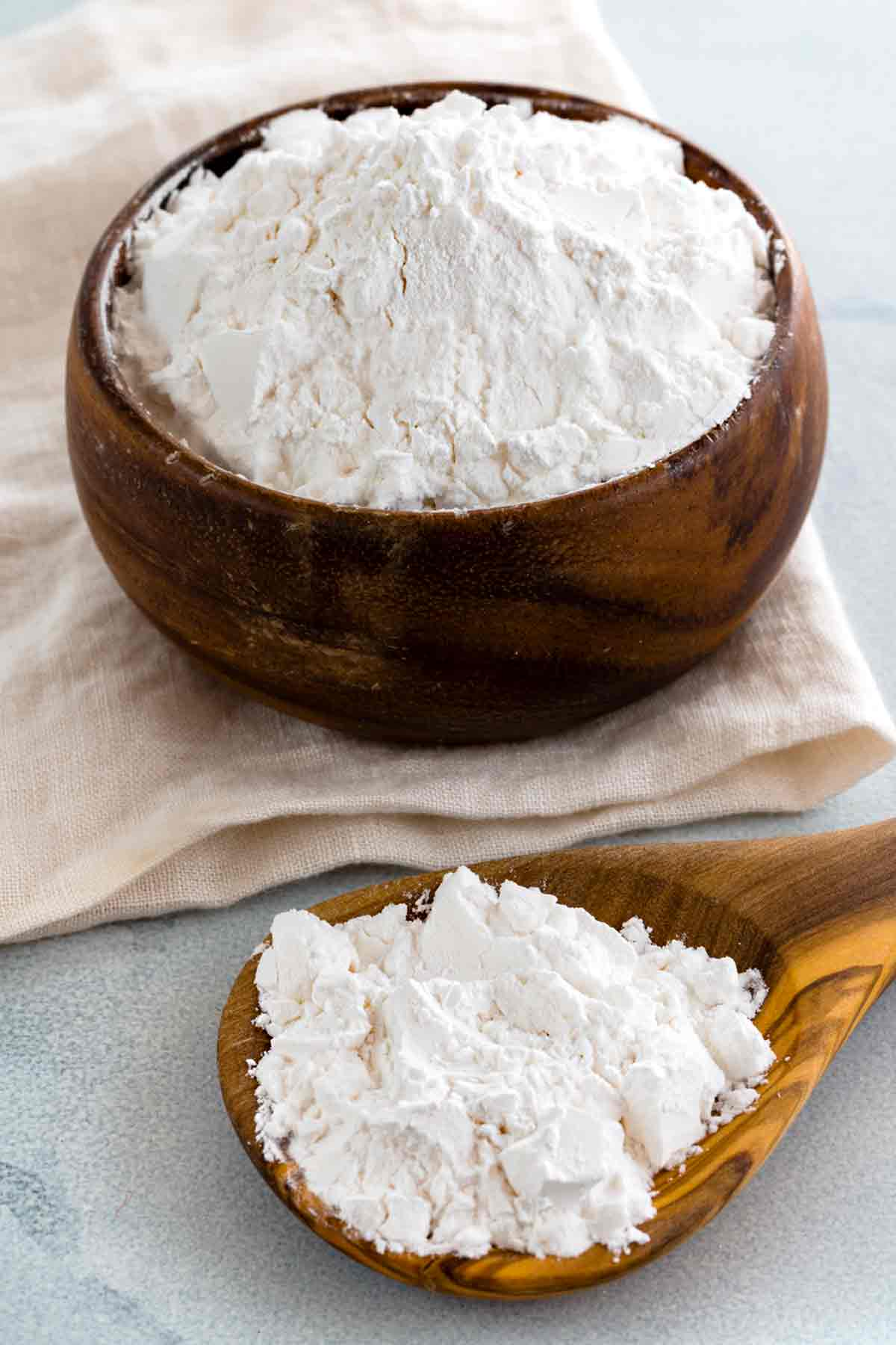 Arrowroot powder in a wooden jar and on a wooden spoon
