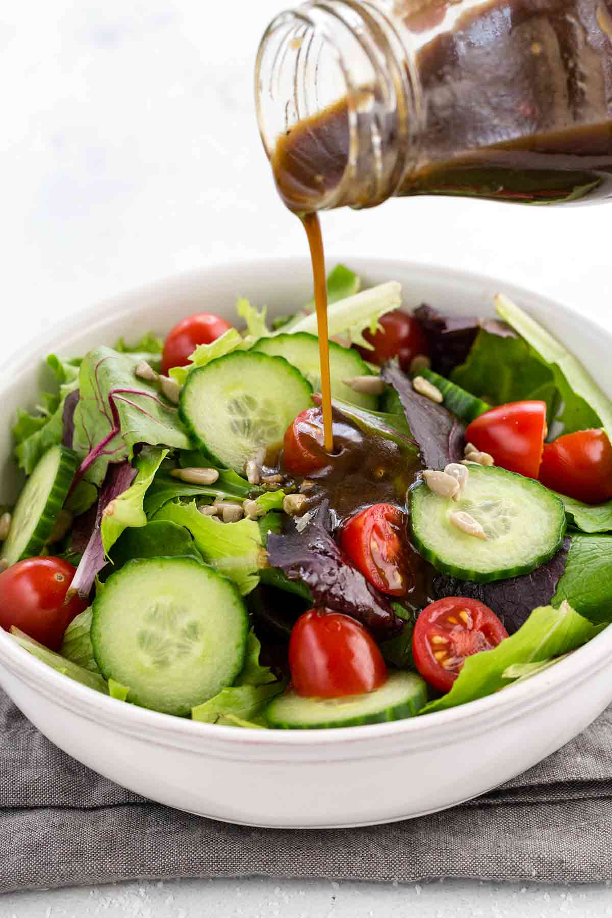 Pouring balsamic vinaigrette out of a glass jar onto a green salad