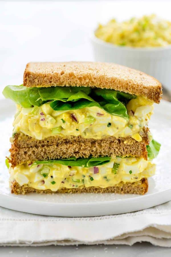 Photo of an egg salad sandwich split down the middle and stacked on top of eachother