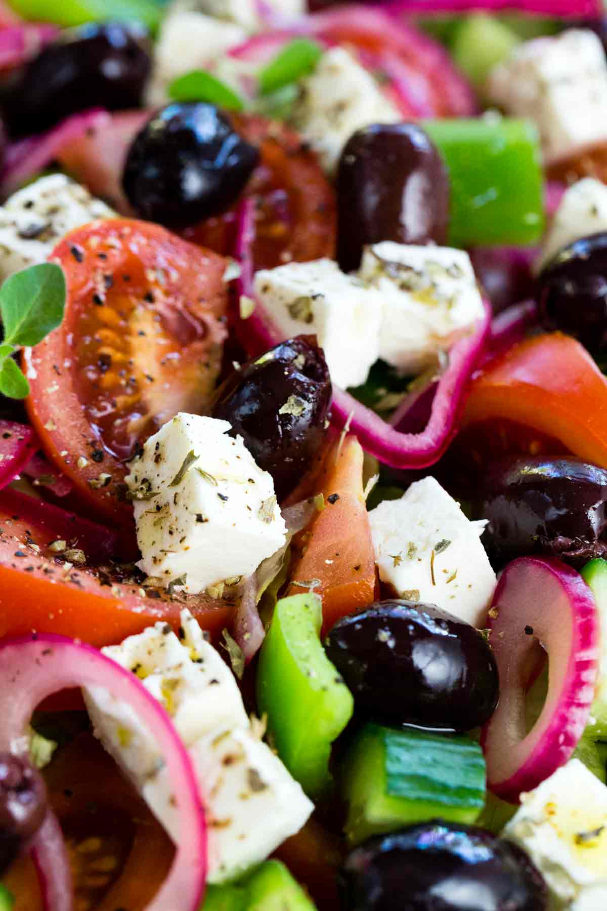 Closeup of tomatoes, feta cheese, olives and other ingredients in a Greek salad