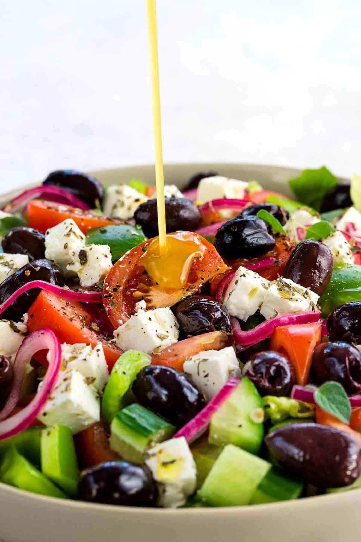 pouring salad dressing over a greek salad