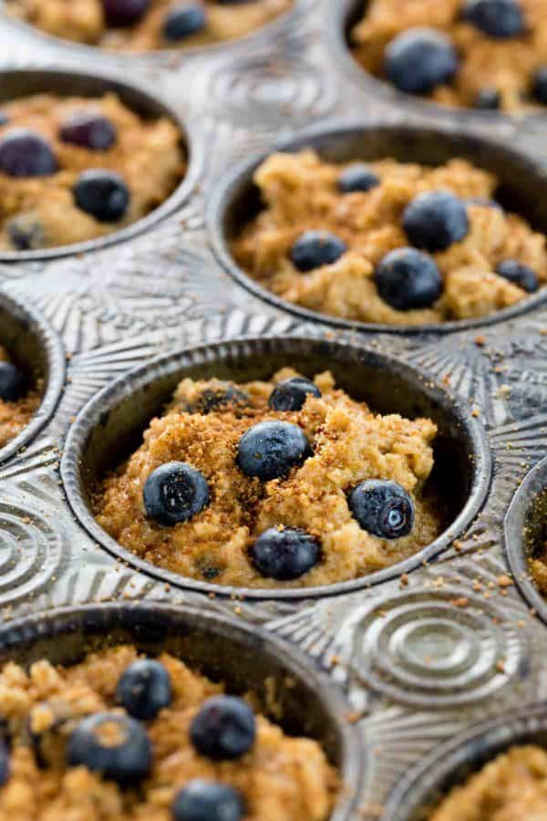 Muffin tin filled with blueberries and batter before being baked