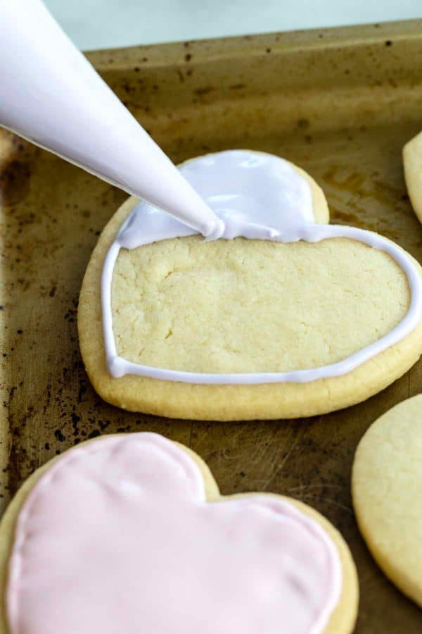 Piping bag applying flood icing to a heart-shaped cookie on a baking sheet