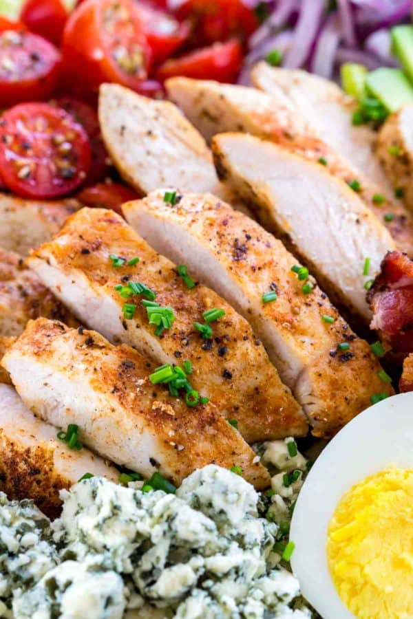 Close up photo of sliced chicken breasts in a cobb salad