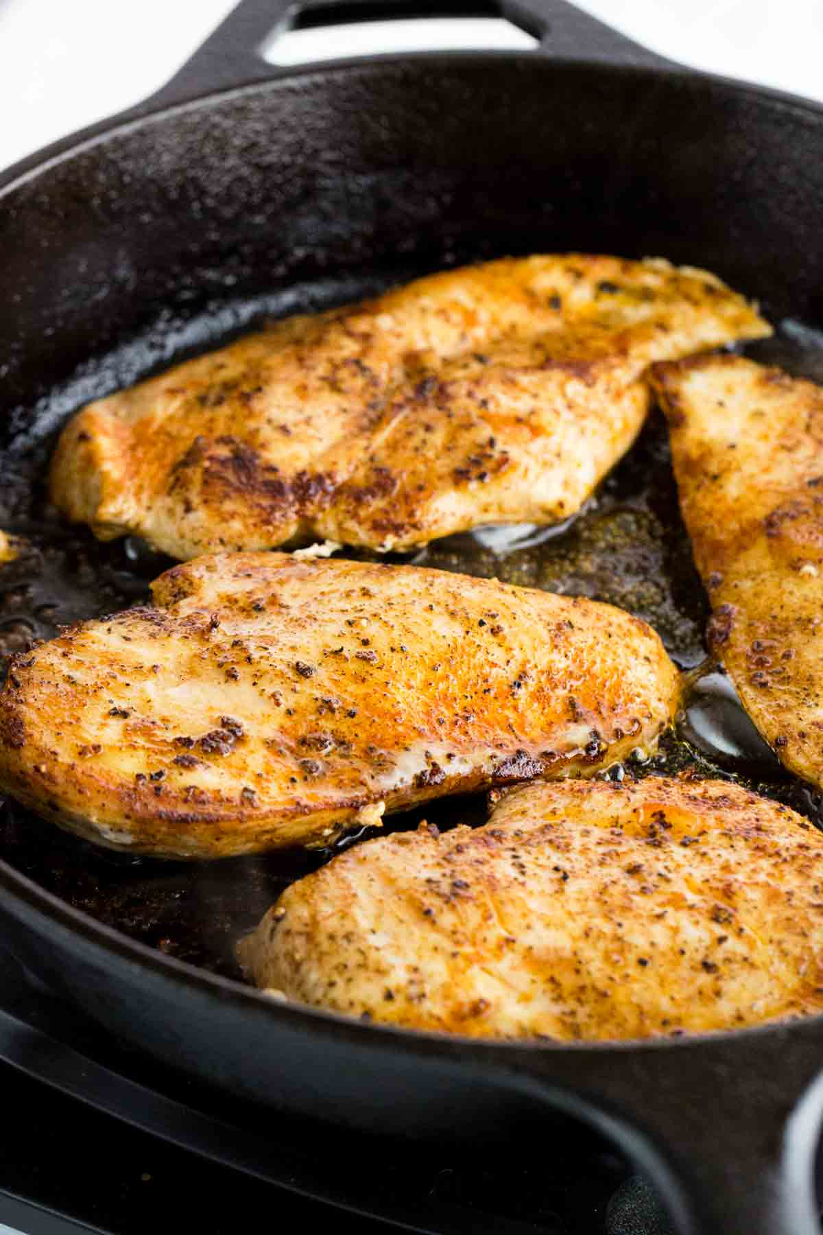 Four seasoned chicken breasts cooking in a cast iron skillet