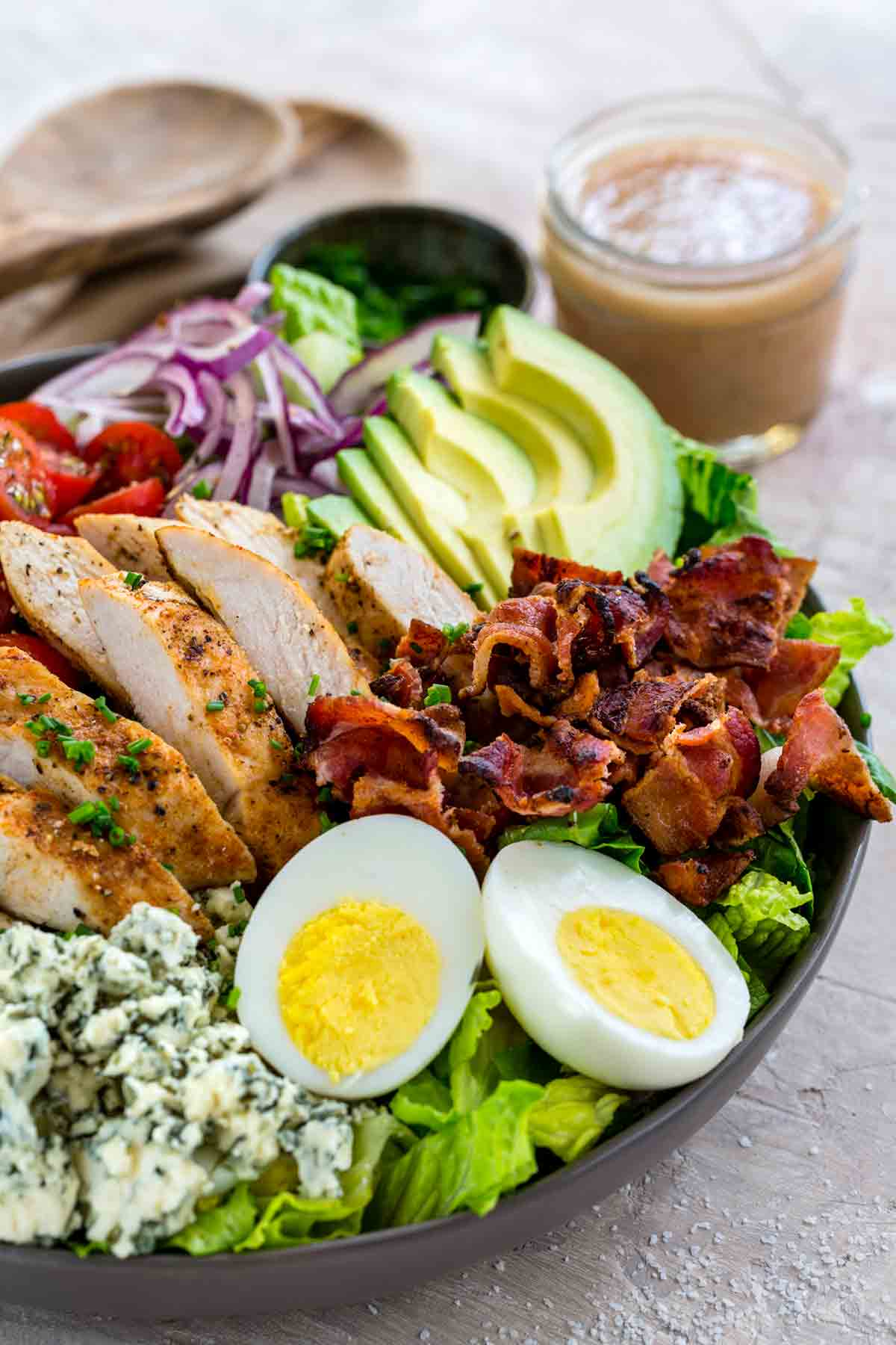 A beautiful cobb salad on a table next to a jar of homemade dressing