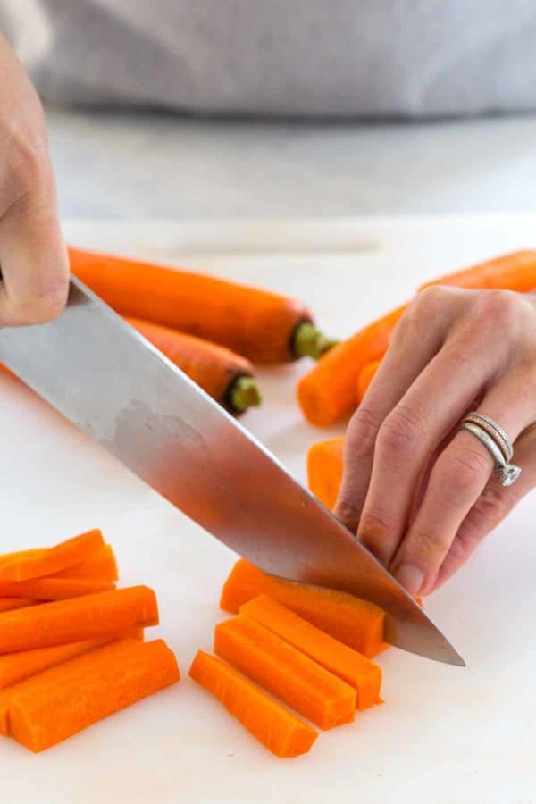 Photo of person slicing carrots with a knife