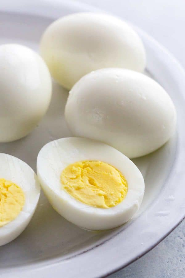 Hard boiled eggs on a white plate with one sliced open showing the yellow center