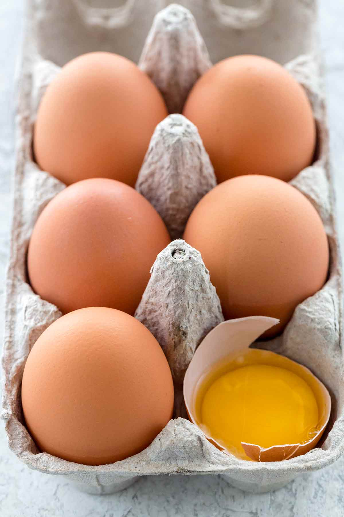 Open carton of brown eggs