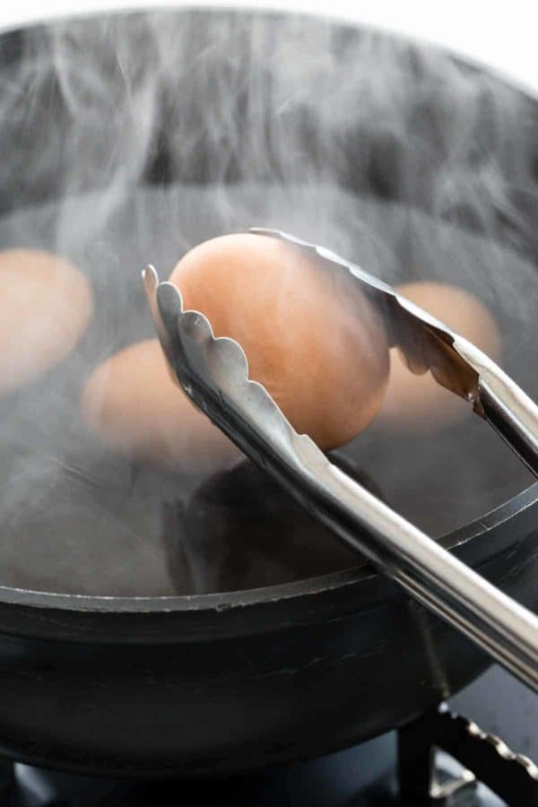 Metal tongs picking up a hard-boiled egg out of a boiling pot of water