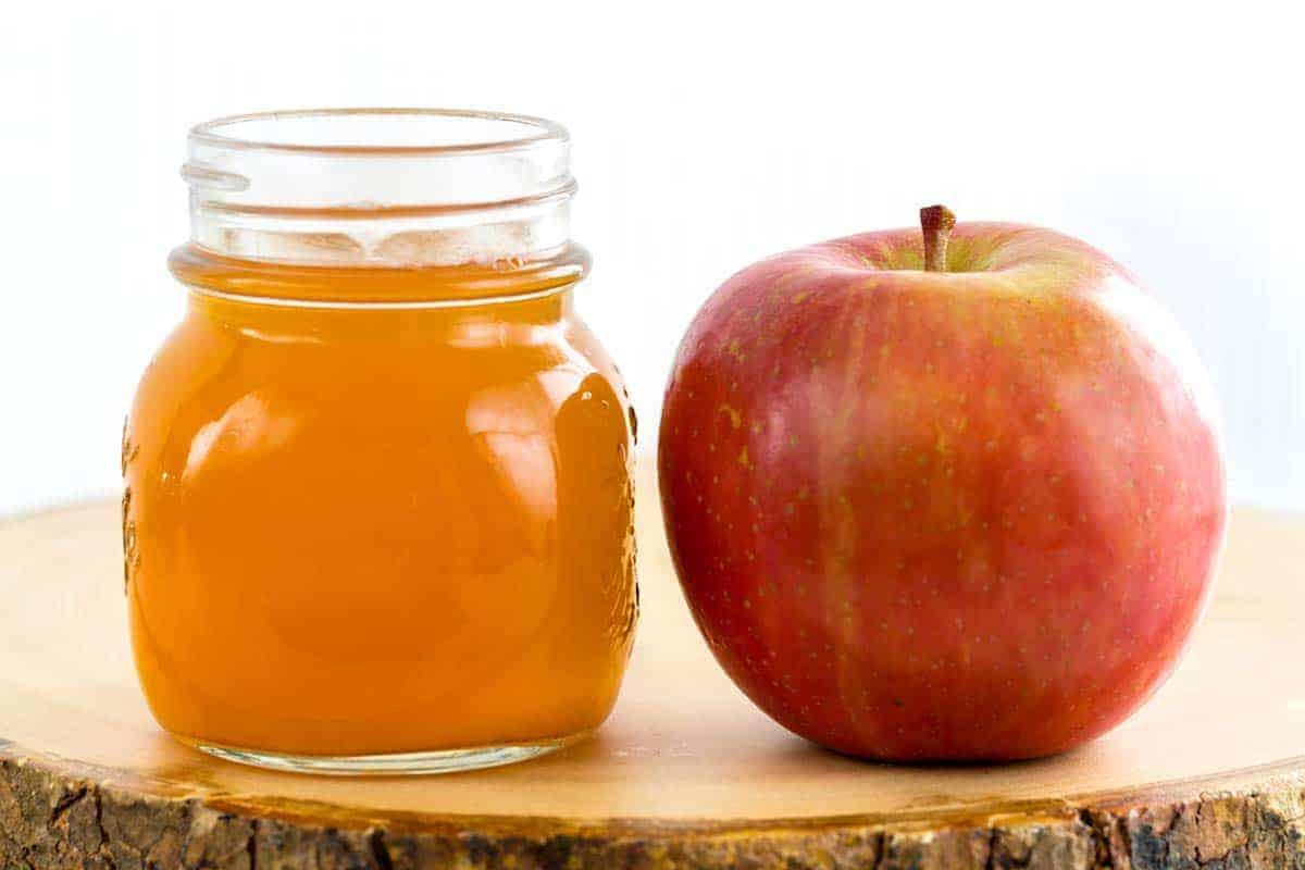 Glass jar of apple cider vinegar next to a red apple