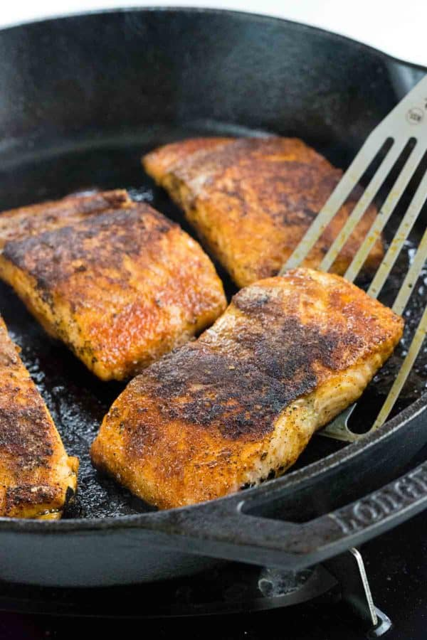 Fish spatula lifting blackened salmon out of a cast iron skillet