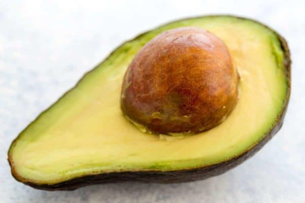 Photo of a sliced avocado with seed still inside