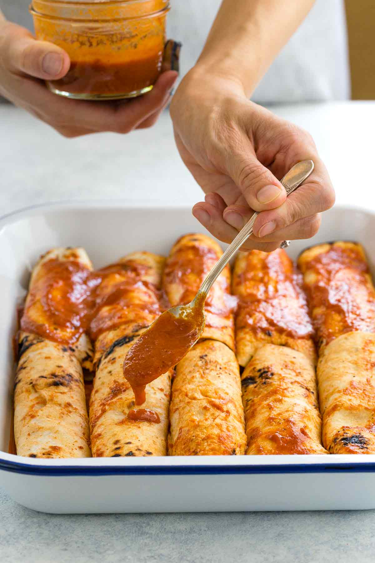 Photo of a person adding red sauce to the top of chicken enchiladas