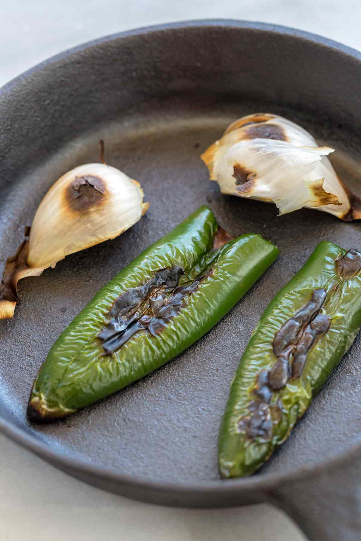 Roasting slices  of jalapeno and unpeeled garlic cloves in a small pan