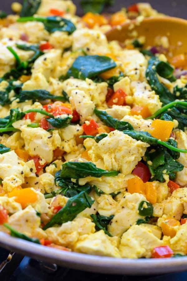 Vegan tofu scrambled eggs with vegetables in a frying pan