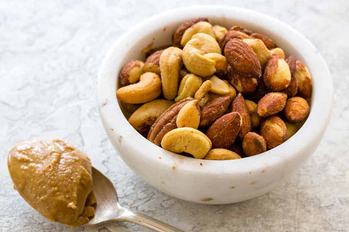 Bowl of nuts next to a spoon of peanut butter