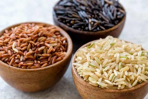 Small wooden bowls filled with different types of rice