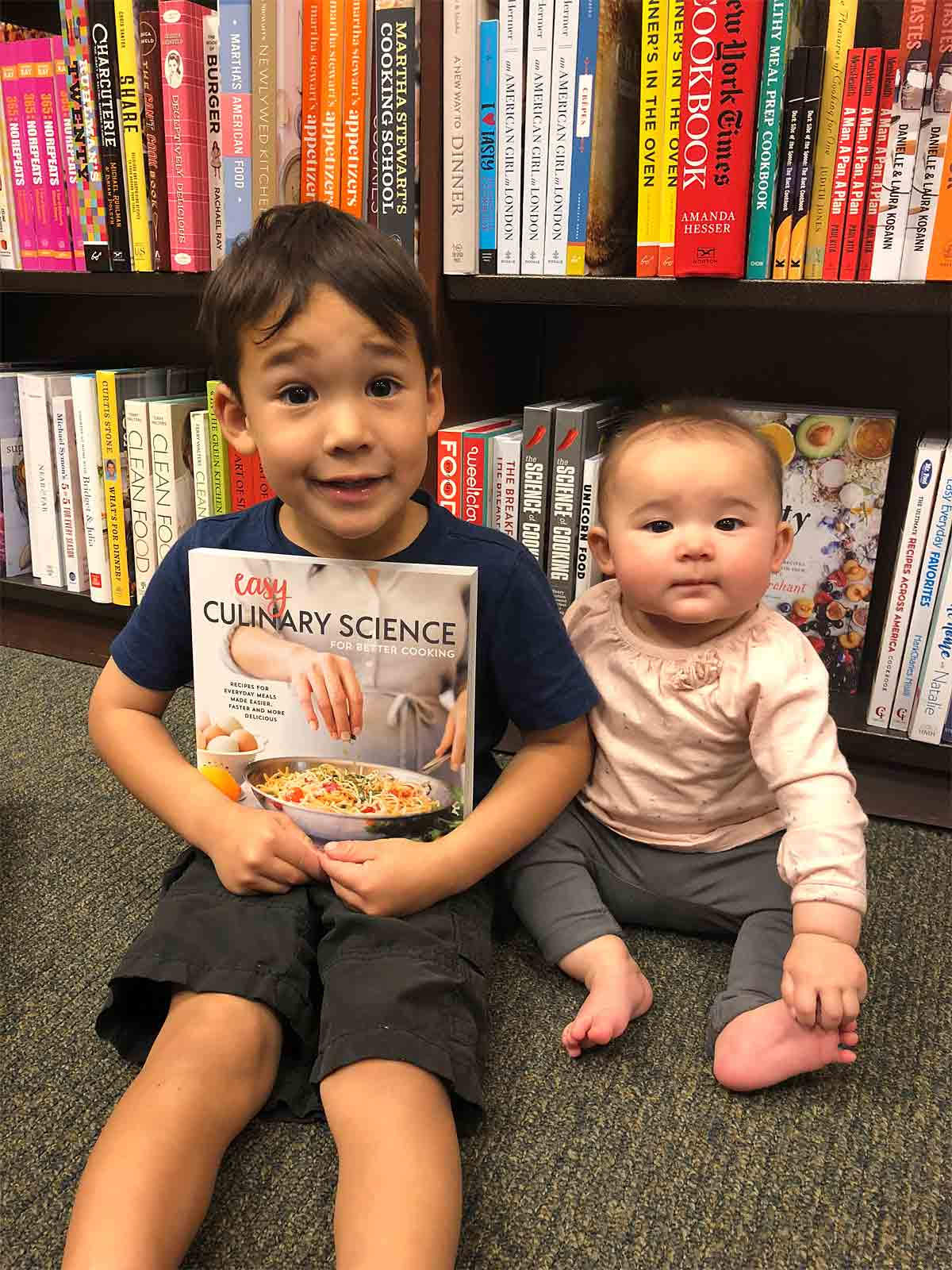 James and Olivia holding a copy of mommy's cookbook