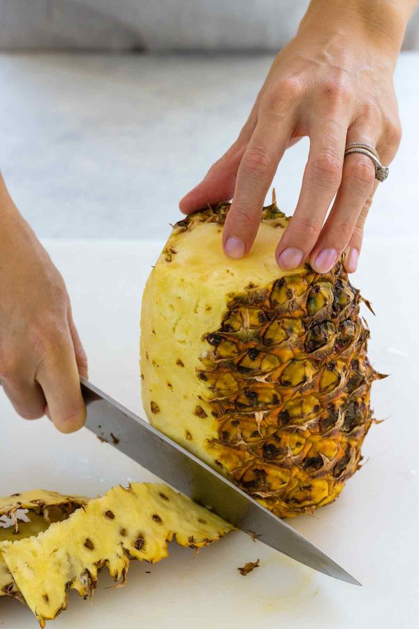 Person holding a pineapple up and trimming the sides off
