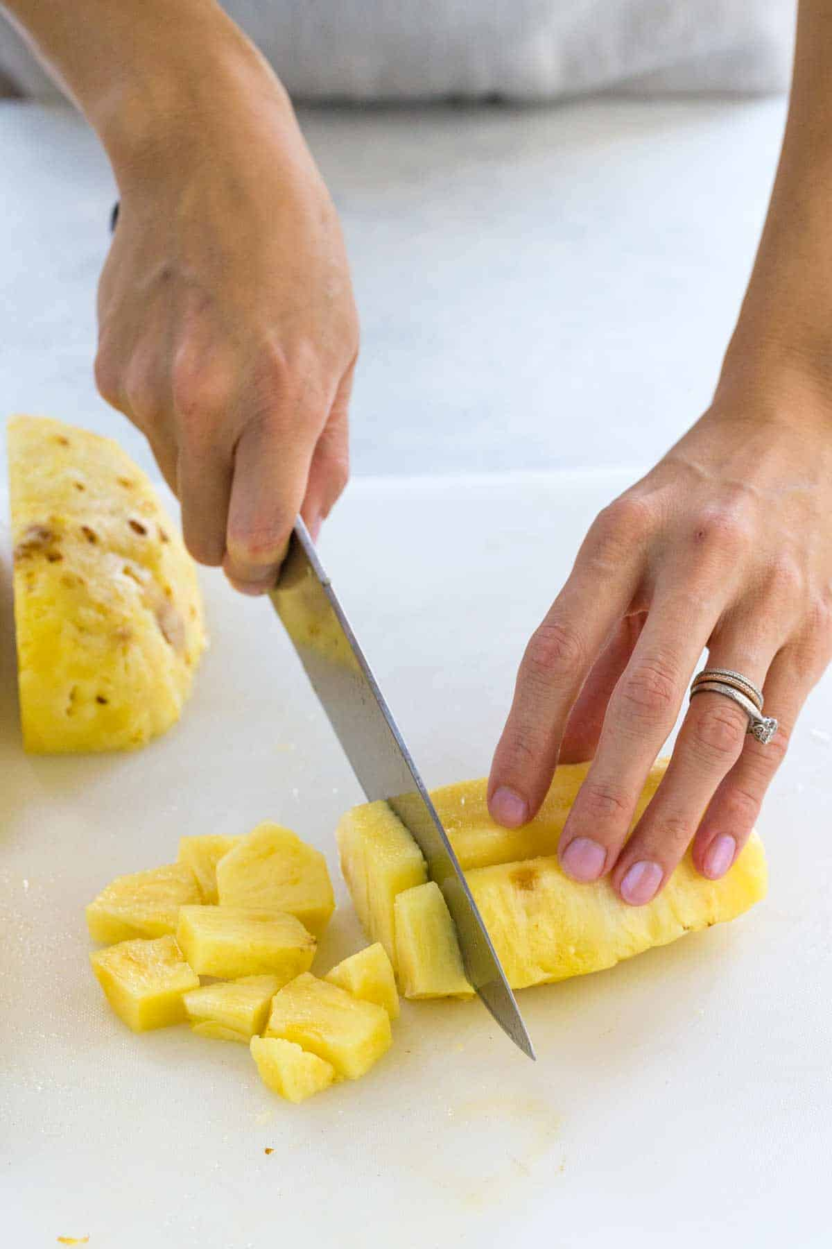 Person using a knife to cut pineapple into small chunks
