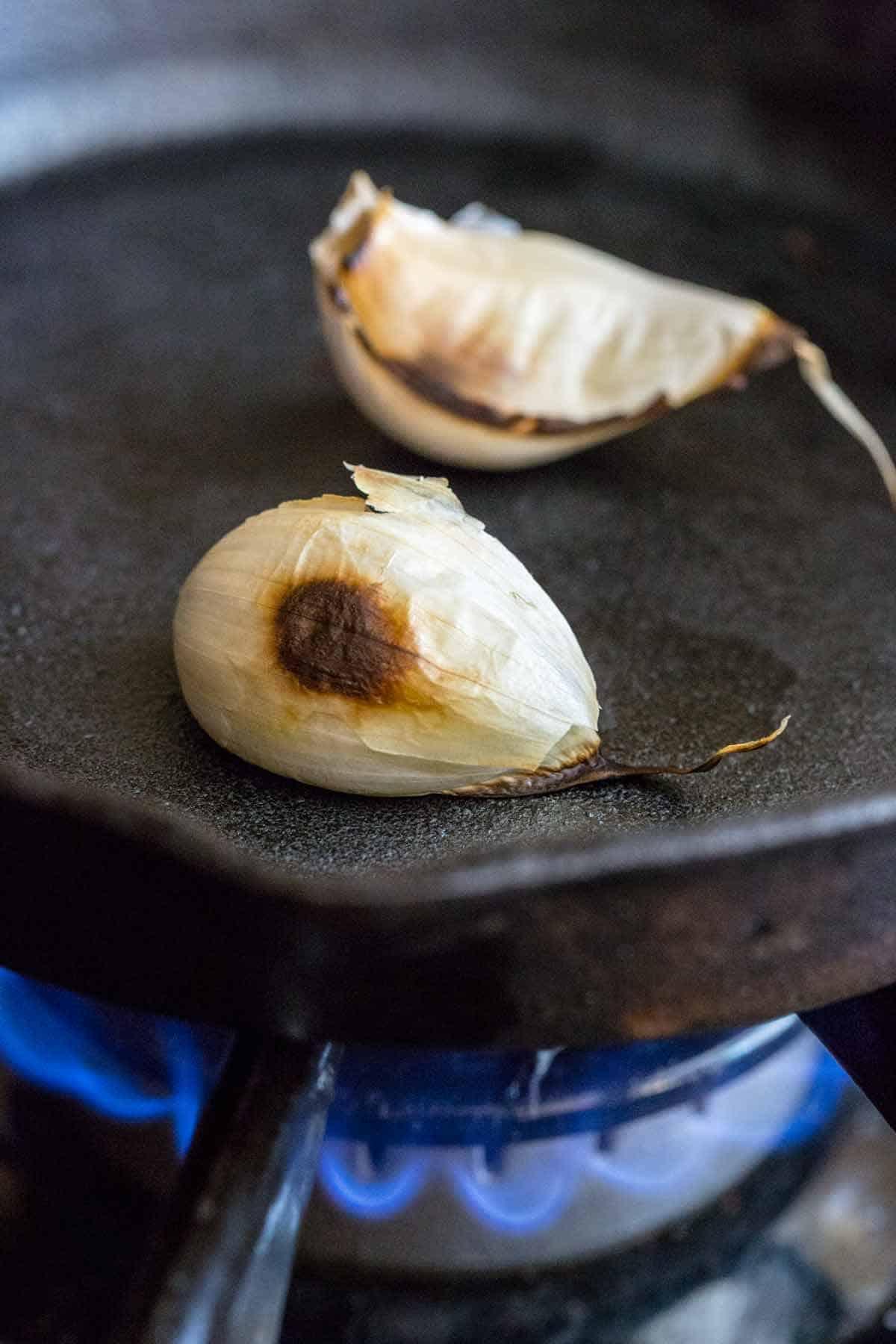 Garlic cloves roasting on a cast iron skillet