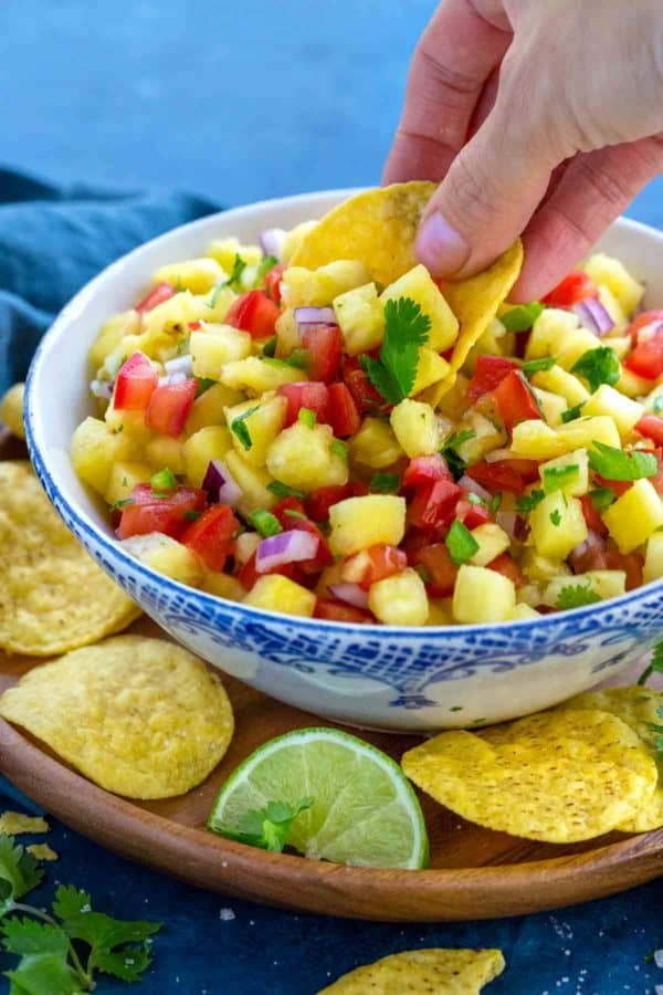 Photo of a hand dipping a tortilla chip into a bowl of pineapple salsa