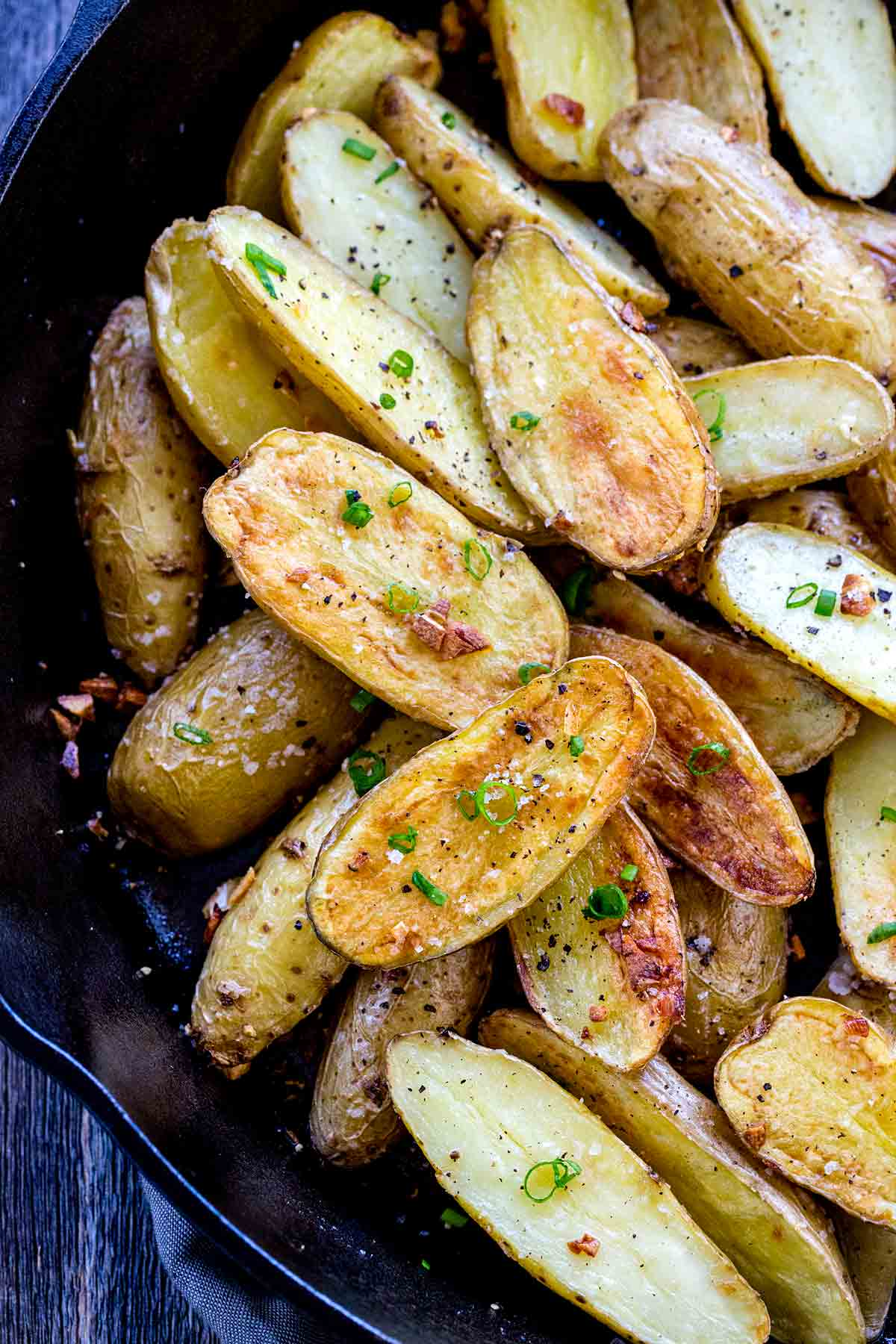 Top down photo of roasted fingerling potatoes in a cast iron pan