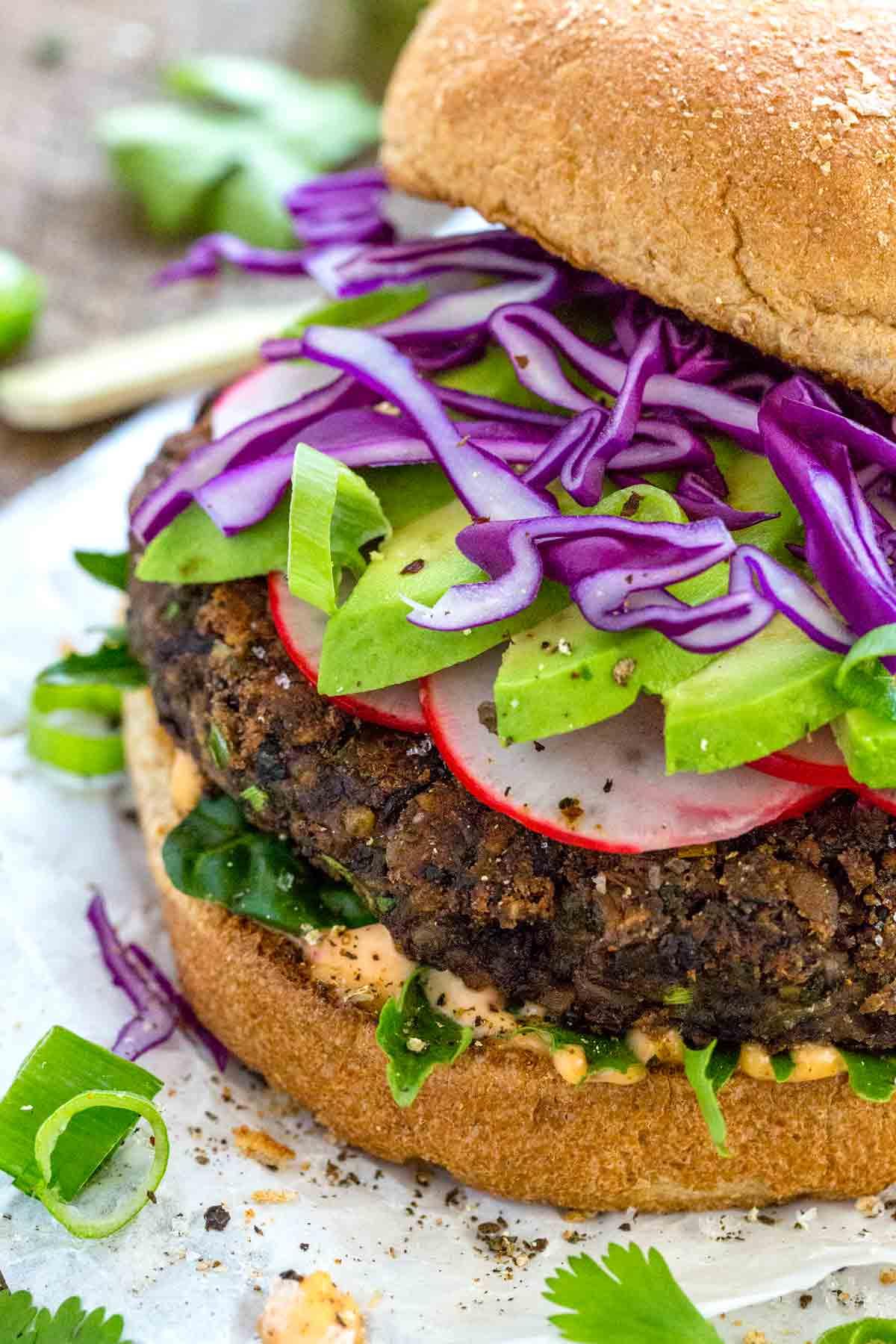 close up photo of a black bean burger with avocado slices and garnish