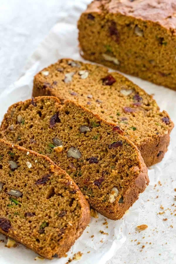 sliced zucchini bread showing pieces of cranberries and nuts inside