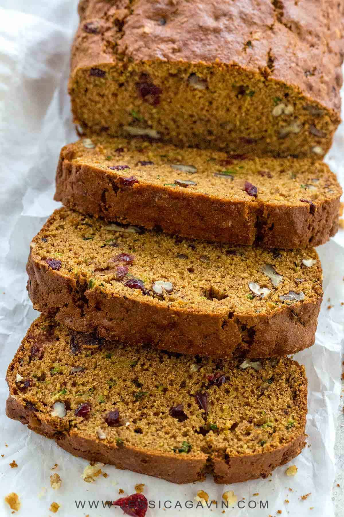 Zucchini bread is an easy to make, tender treat with a cake-like texture. Each slice is packed with healthy grated zucchini, pecans, cranberries, cinnamon, nutmeg, and whole wheat flour. #zucchinibread #bread #zucchini
