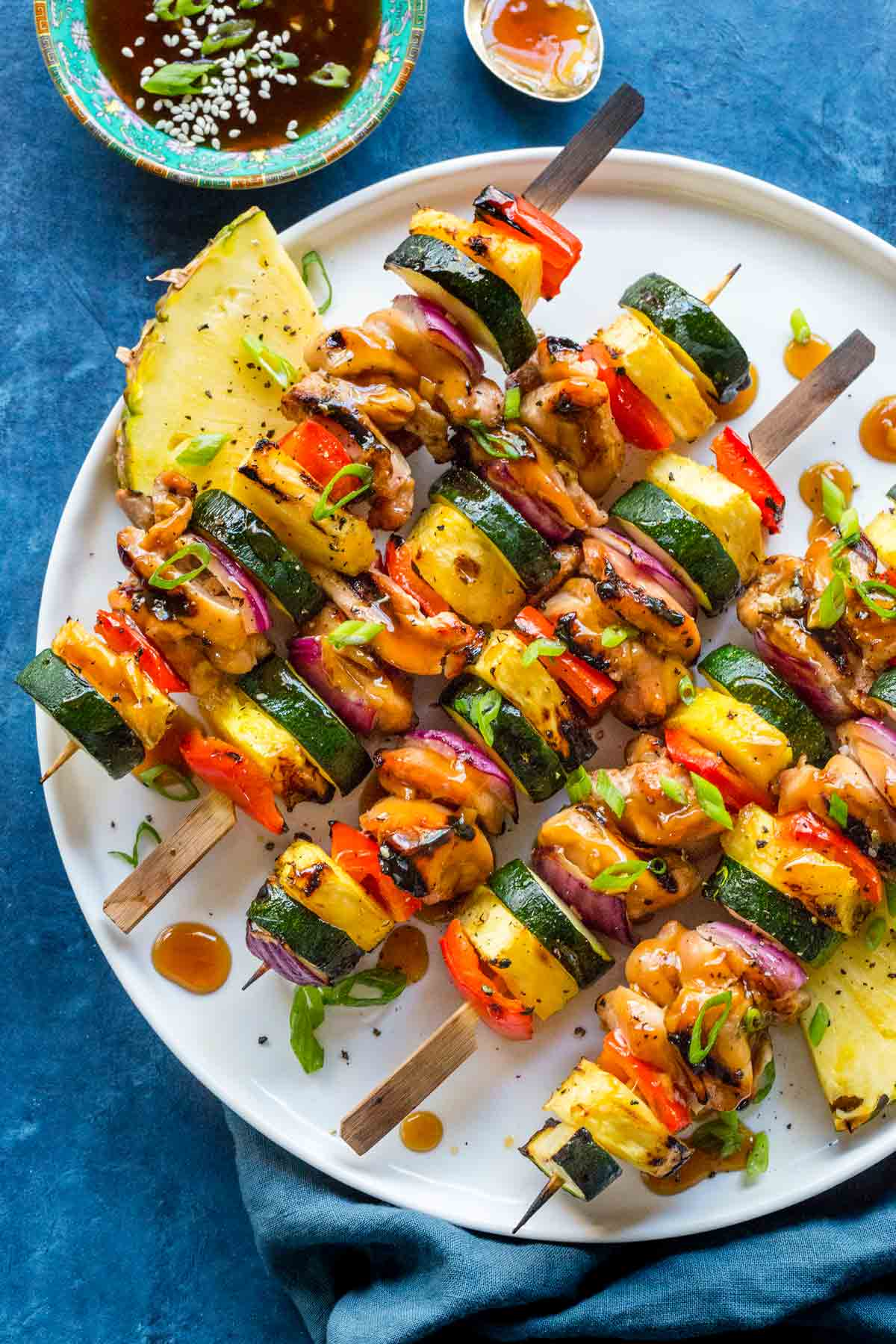 Plate of hawaiian chicken and pineapple chunks on wooden skewers