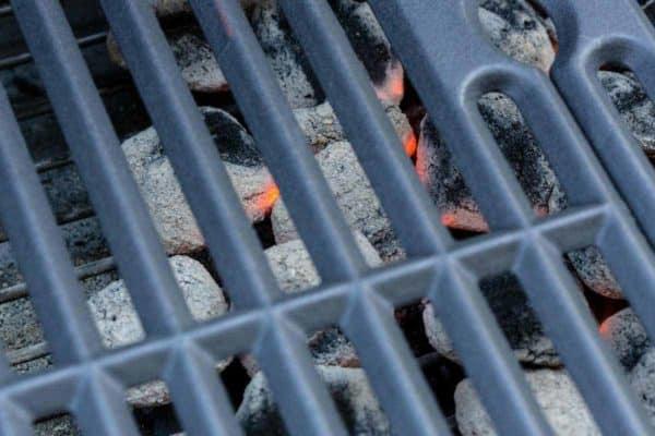Hot coals under grilling grates of a barbecue