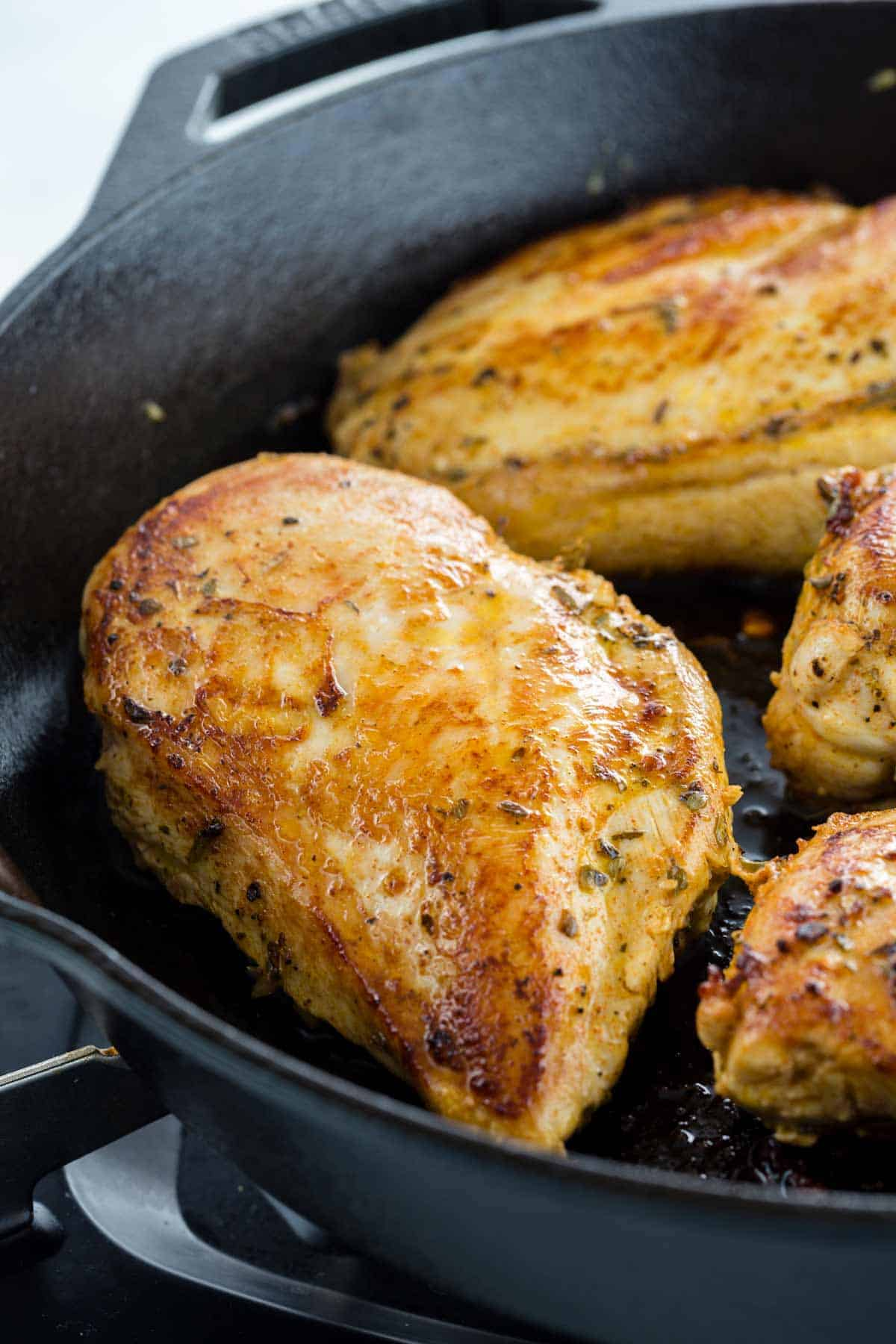 Chicken breast with maillard reaction showing a golden brown crust cooking in a cast iron pan