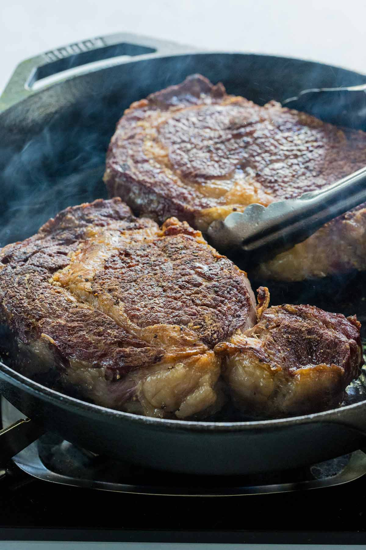 Two ribeye steaks cooking in a cast iron skillet