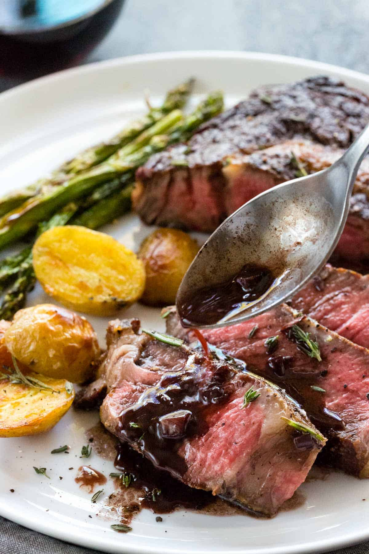 Spoon pouring red wine reduction sauce over slices of ribeye steak