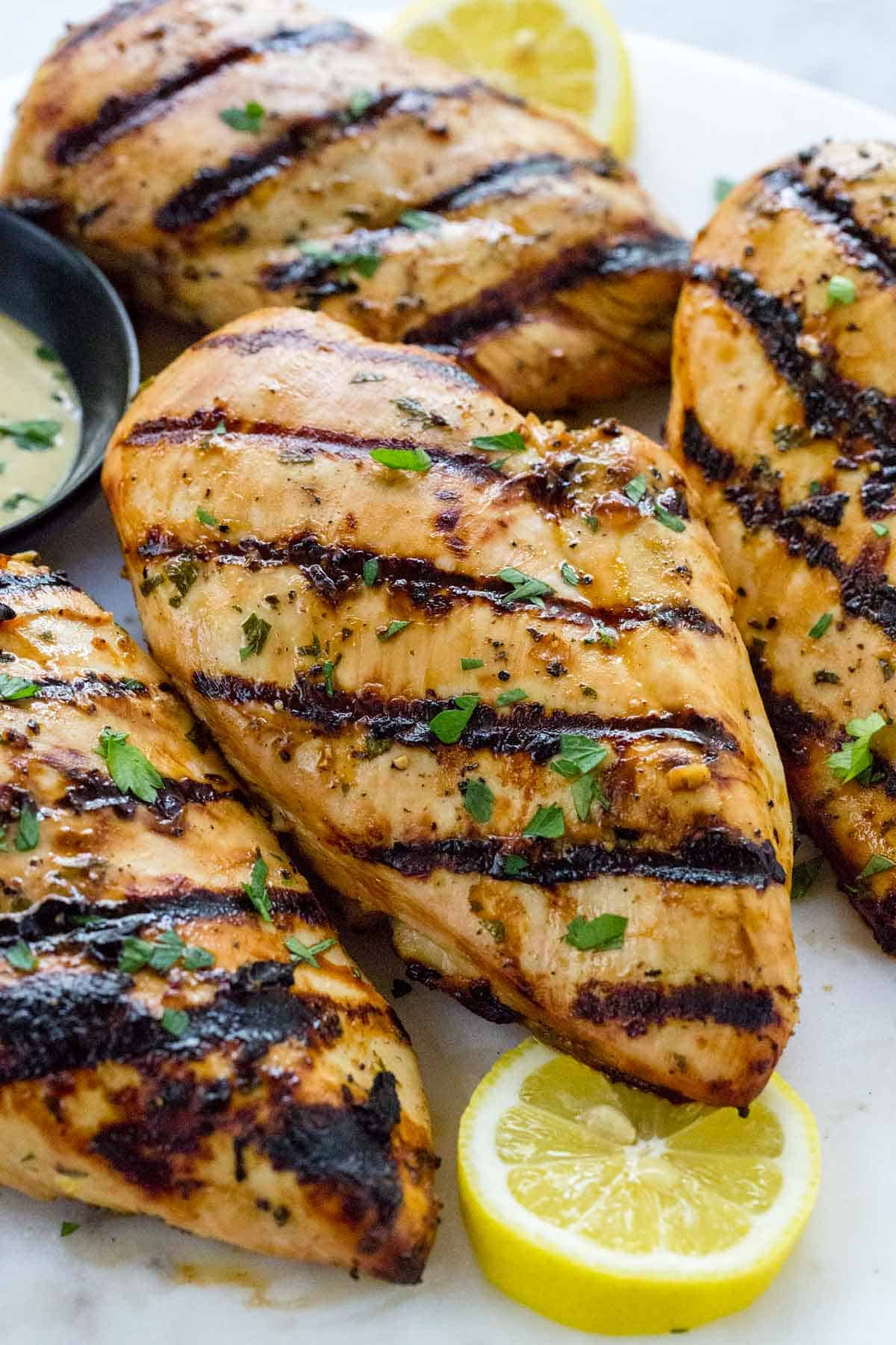 Grilled chicken breasts served on a plate with lemon