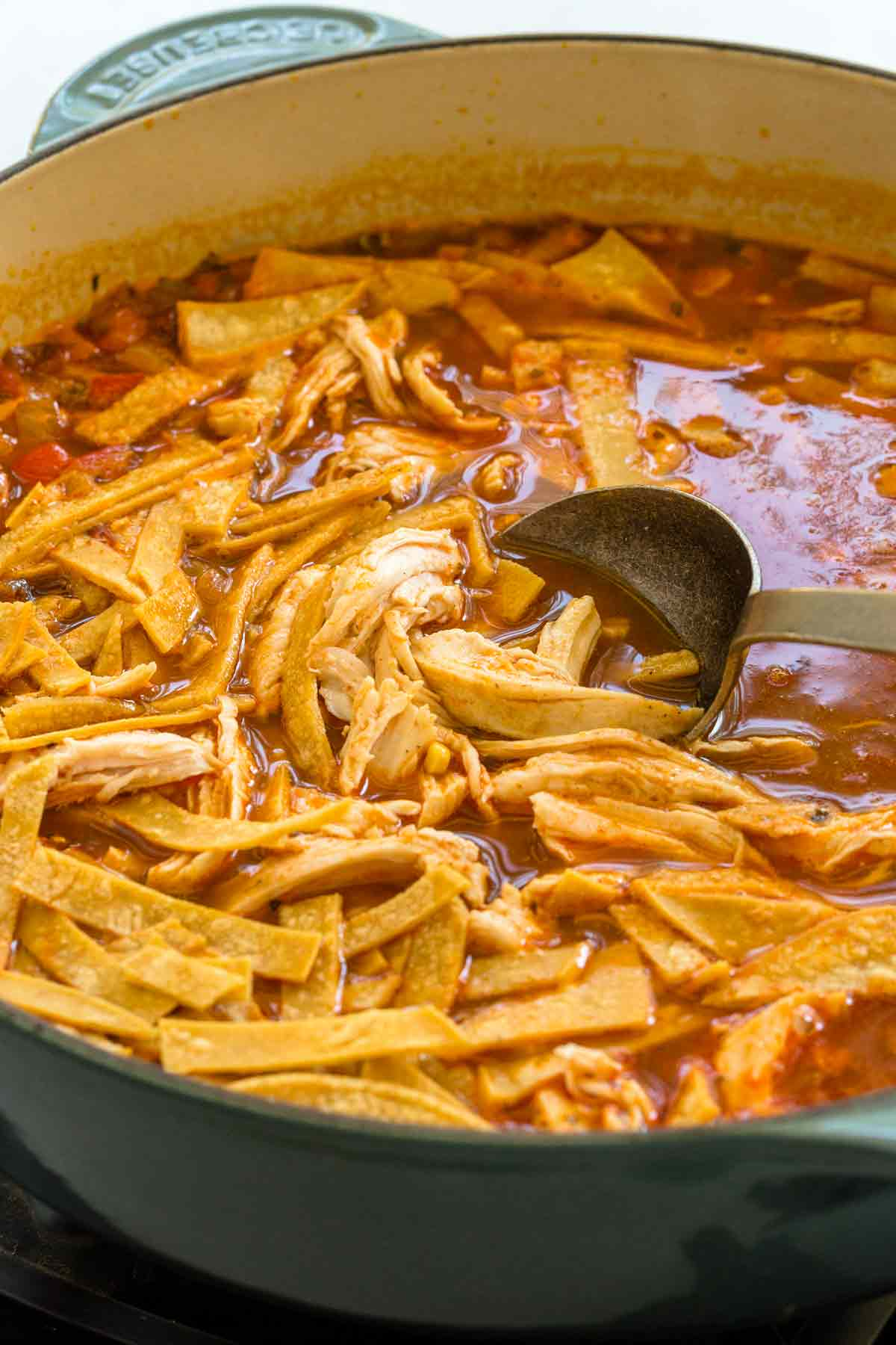 tortilla strips being mixed into mexican chicken soup