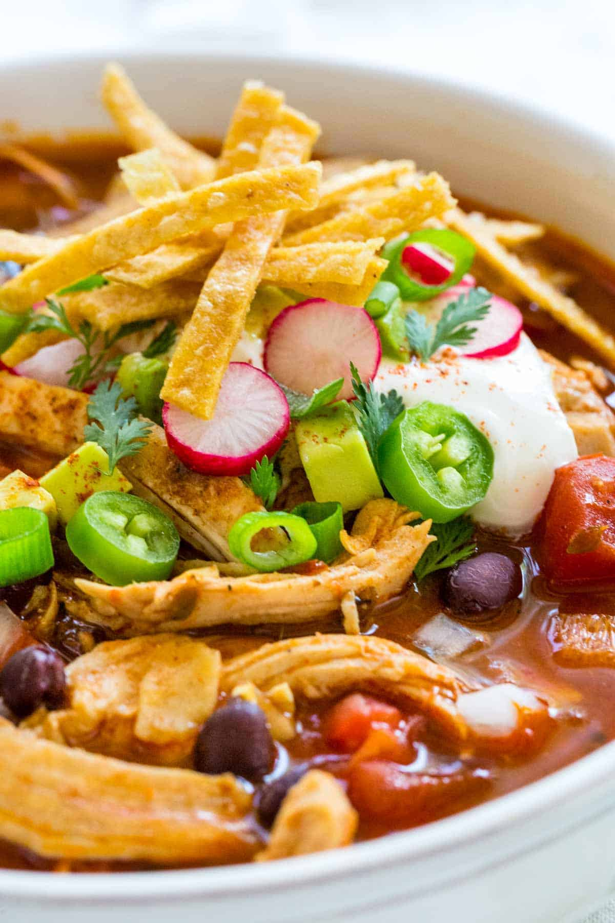 chicken tortilla soup topped with sour cream and jalapeños