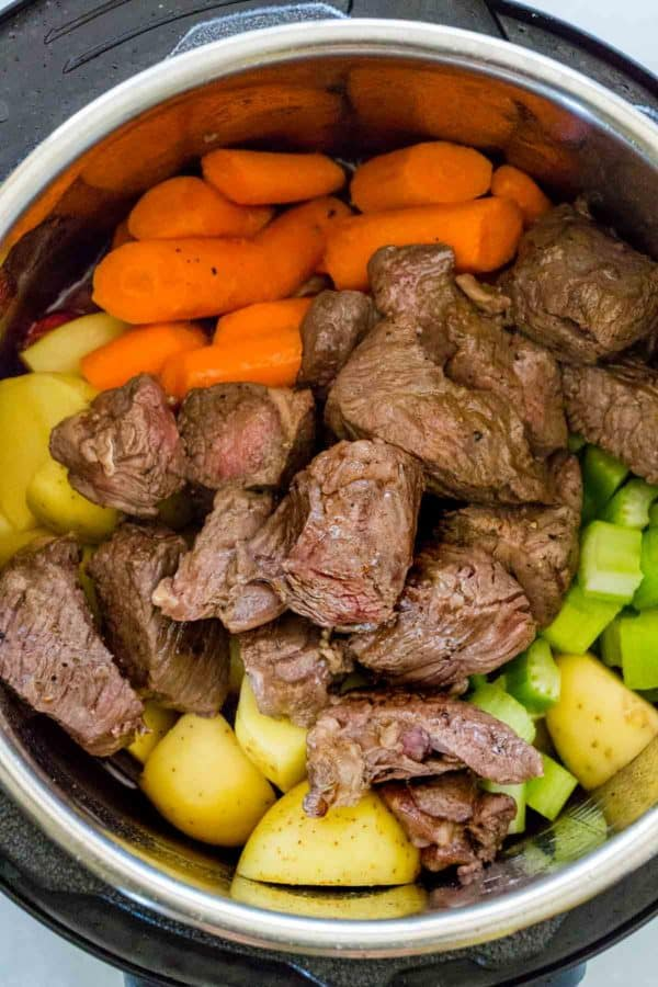 Ingredients for beef stew placed inside an Instant Pot