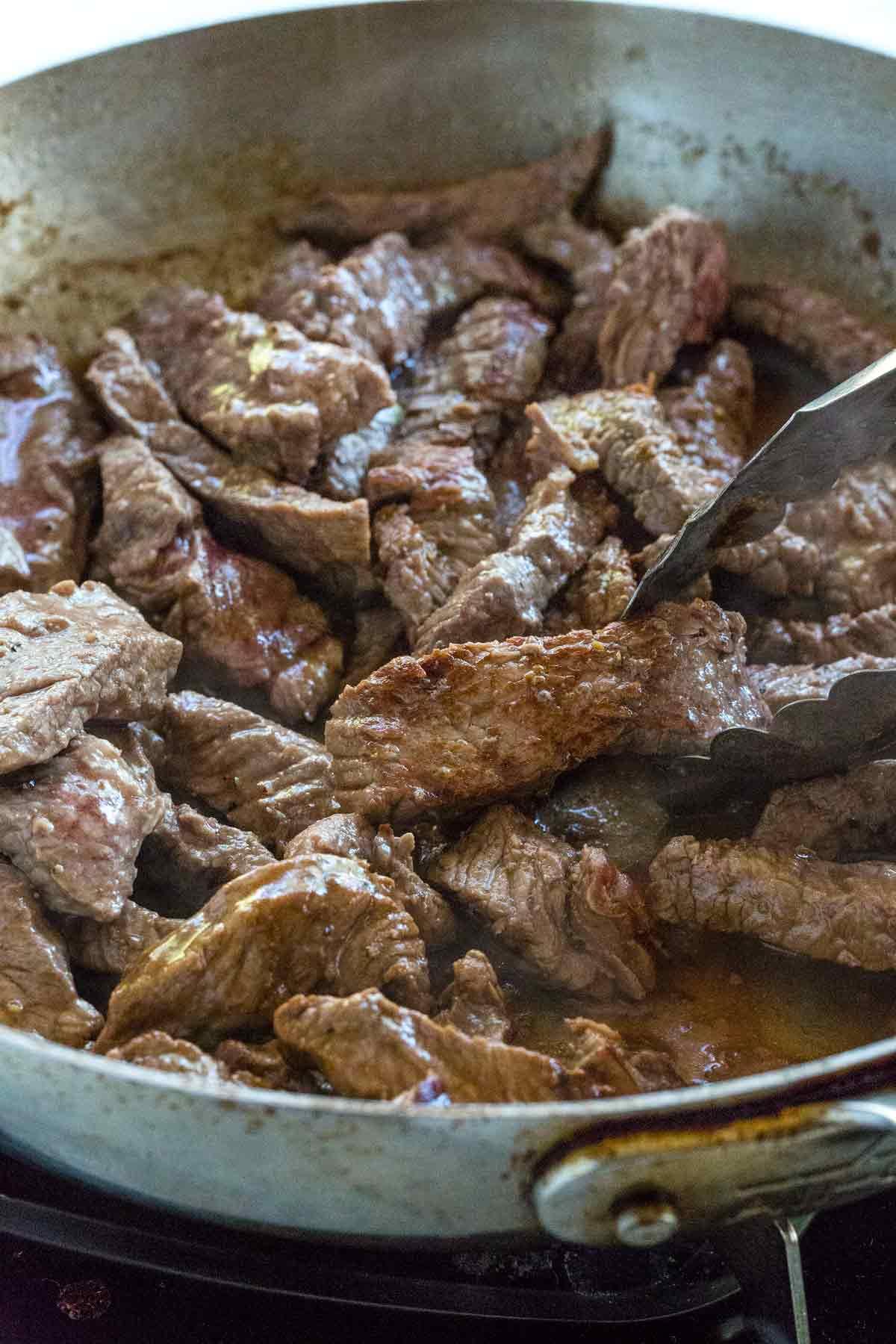 Sautéing sirloin steak in a pan