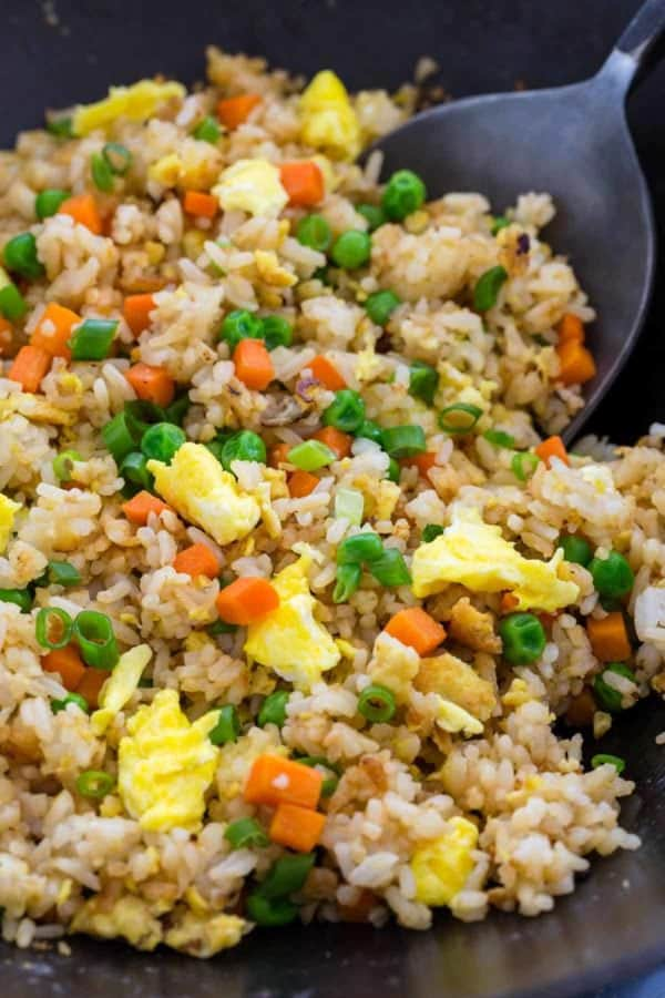 Wok spatula mixing fried rice in a pan