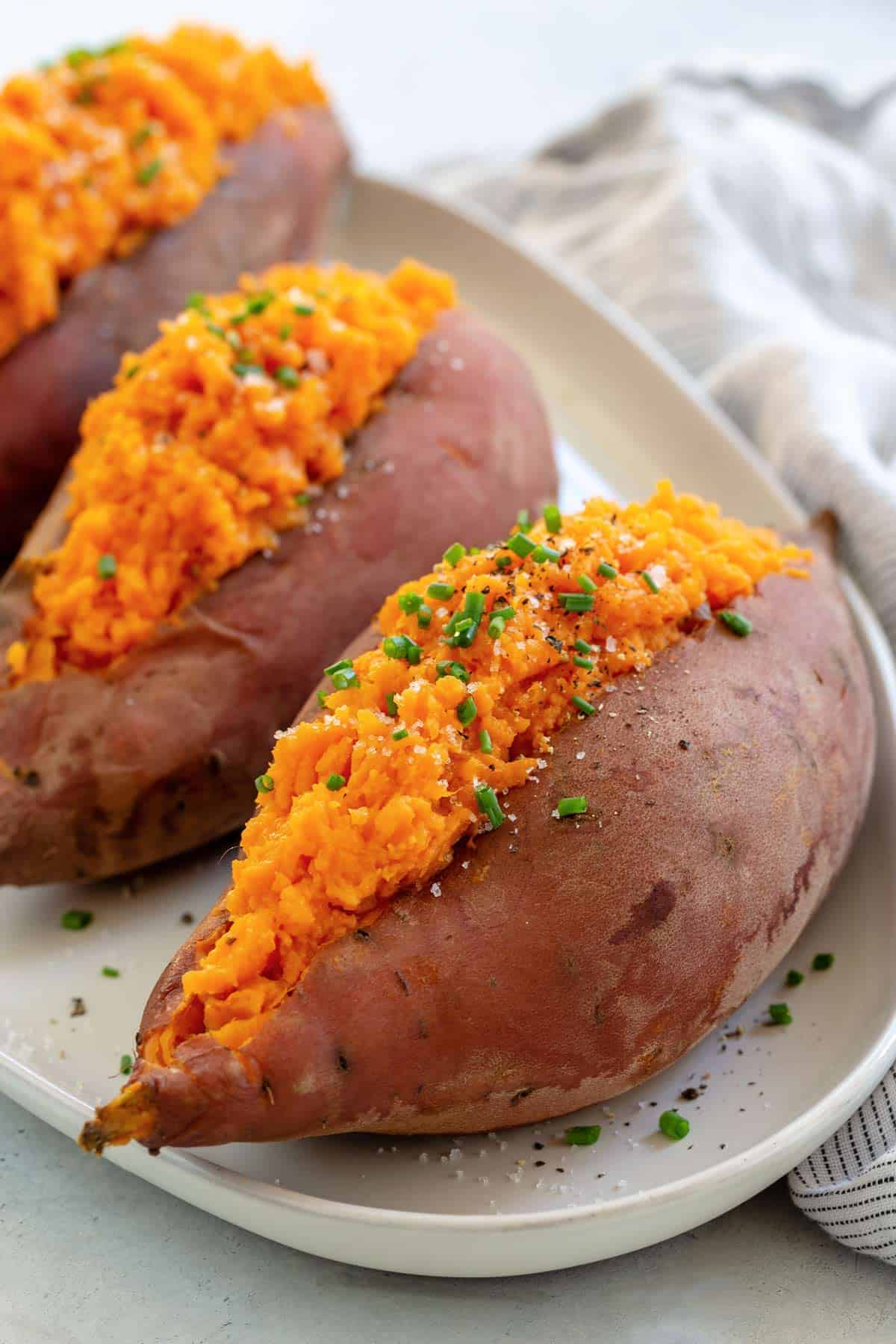 Three baked sweet potatoes on a white serving platter