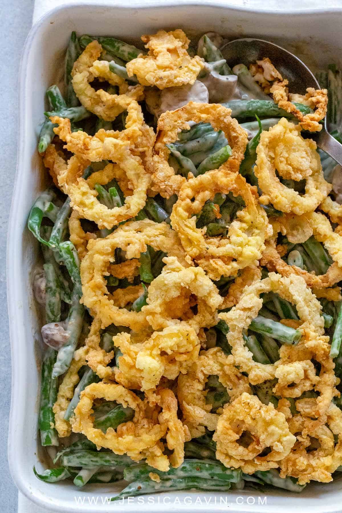 This green bean casserole side dish features crunchy beans tossed in a creamy mushroom sauce and topped with crispy fried onions rings. #greenbeans #thanksgiving #sidedish #onionrings #casserole